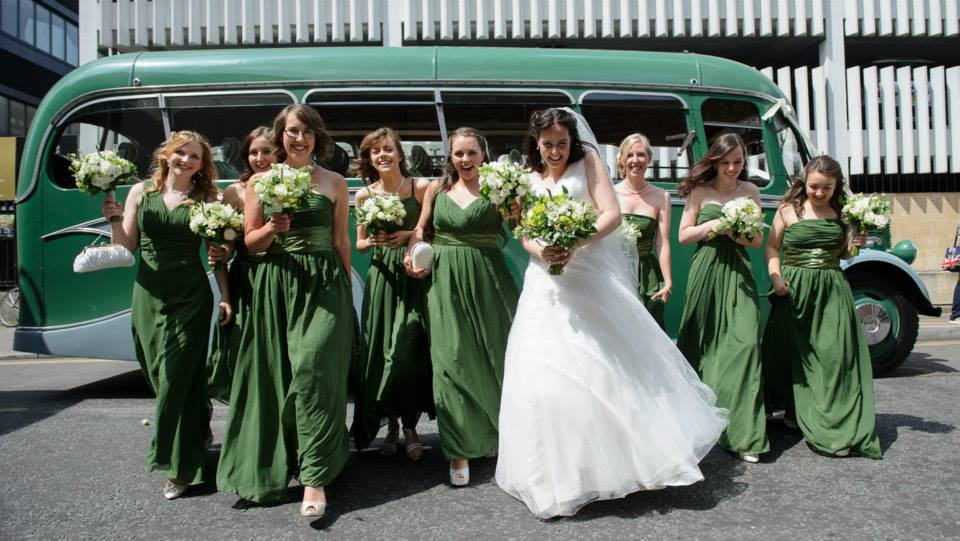 dews-coaches-bride-and-bridesmaids-walking-in-front-of-vintage-bus